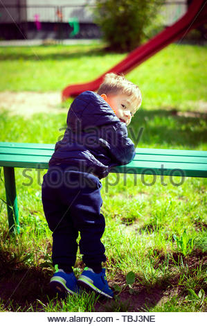 Young boy with a blue jacket leaning on a wooden - Stock Image