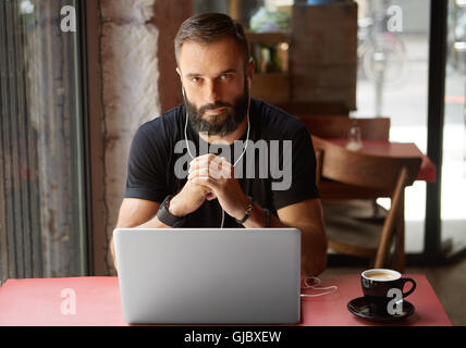 Handsome Young Bearded Businessman Wearing Black Tshirt Working Laptop Urban Cafe.Man Sitting Wood Table Cup Coffee - Stock Image