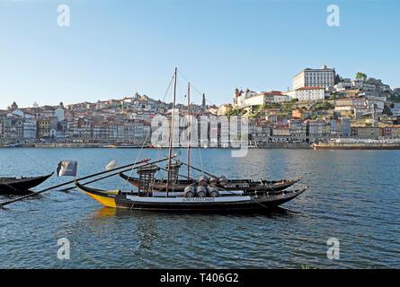 A view of a boat with wine barrels on the River Douro, Ribeira waterfront riverside & cityscape from Vila Nova de Gaia in Porto Portugal EU   KATHY - Stock Image