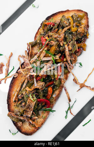 spicy dried squid and roast vegetables toasted open sandwich tapas snack in portugal - Stock Image