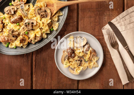 Mushroom and cheese pasta. Farfalle with cremini and green peas, shot from above on a dark rustic wooden background - Stock Image
