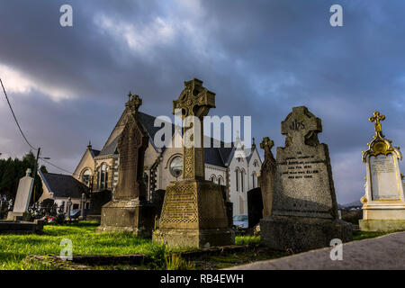 Ardara, County Donegal, Ireland. 7th January 2019. Low winter sunlight shines on gravestones in the cemetery of The Church of the Holy Family after passing showers. Credit: Richard Wayman/Alamy Live News - Stock Image