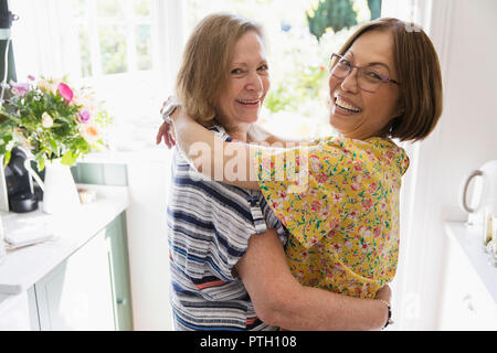 Portrait affectionate senior lesbian couple hugging in kitchen - Stock Image