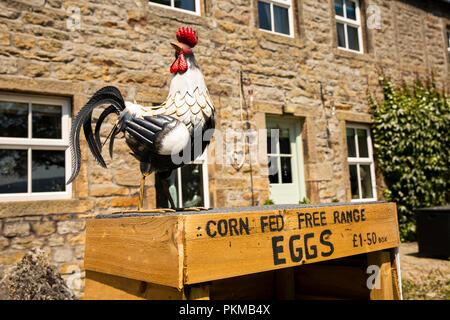 UK, Yorkshire, Wharfedale, Burnsall, village green, artificial hen on box selling corn fed free range eggs - Stock Image