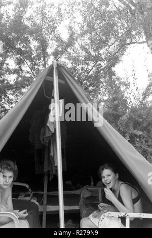 two young females sitting having a meal in the entrance of their tent while camping 1960s hungary - Stock Image