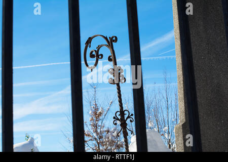 Wrought iron decorative object seen through the metal bar fence. A beautiful winter sky is visible in the background. - Stock Image