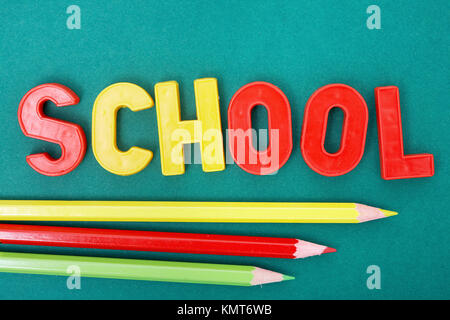 Image of word 'school' with three colorful pencils below - Stock Image