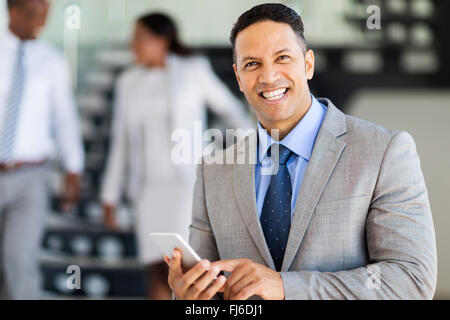 smiling middle aged businessman using smart phone - Stock Image