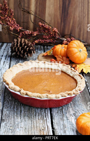 Homemade pumpkin pie in red ceramic pie plate over a rustic wooden background. Extreme shallow depth of field with selective focus. - Stock Image