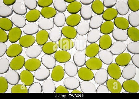 artificial round stones of green and white color, top view. imitation pebbles - Stock Image