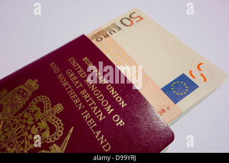 Euro banknotes inside of a British passport. - Stock Image