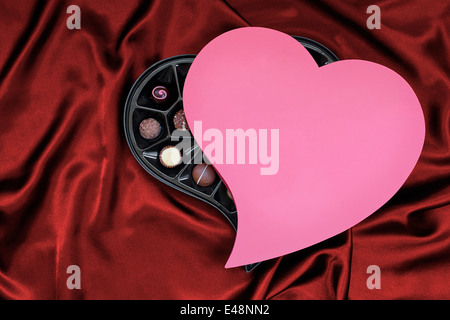 Valentines Day Heart shaped box of luxury chocolates on a red silk background the perfect gift for your wife - Stock Image