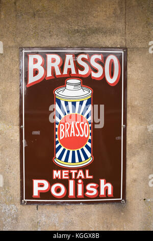 Old metallic advertisement for BRASSO metal polish seen at a heritage steam railway station in Somerset UK - Stock Image