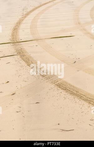 Curving tyre tracks in sand. - Stock Image