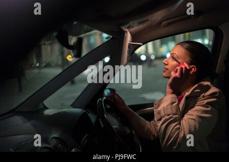 Businesswoman applying mascara in car at night - Stock Image