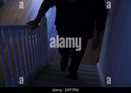 Impending danger as a silhouette of a man walks up a dark stairway. - Stock Image