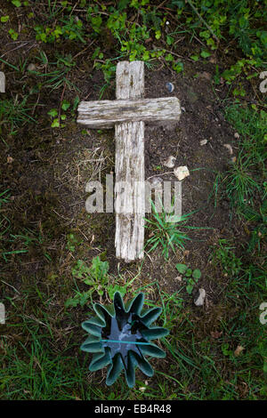 Old wooden cross laid on ground marking grave - Stock Image