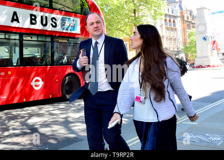 James Slack (official spokesman for 10 Downing Street) and Katie Smith (Senior Press Officer at Prime Minister's Office) in Whitehall, by a bus, May 2 - Stock Image