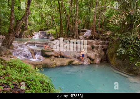 Visitors enjoying Buer Mai Long, the fifth tier of Erawan Waterfall in Kanchanaburi Province, Thailand, with fish swiming in the clear water. - Stock Image