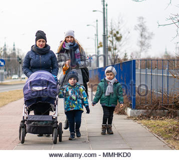 Women and two boys walking on a sidewalk in Poznan, Poland - Stock Image