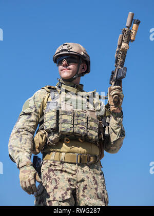 Low angle view of special forces soldier in field uniform with weapon. - Stock Image