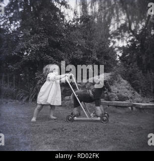 1950s, historical, infant girl in barefeet outside in a back garden pushing a toy horse on wheels, England, UK. - Stock Image