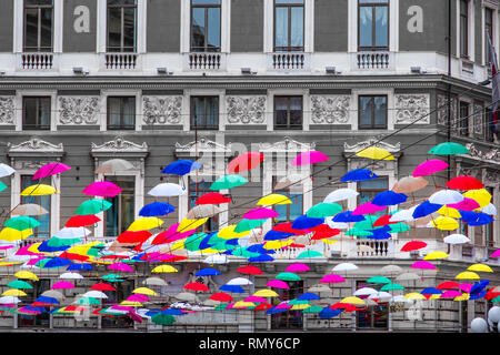 coloful suspended umbrellas hanging n black and white building background . - Stock Image