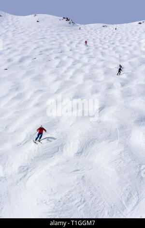 Skiers descending the steep mogul ski hill slope at a mountain in Lake Louise in the Canadian Rockies of Alberta, Canada. - Stock Image