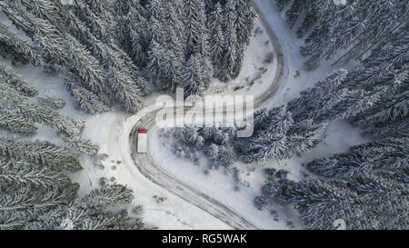 Aerial landscape with meandering snowy winter mountain road with a moving truck - Stock Image