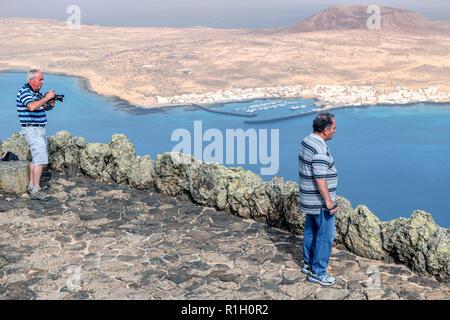 The small fishing and tourist village of Caleta del Sebo on the tiny island of La Graciosa next to Lanzarote Canary islands. Montaña del Mojon is behi - Stock Image
