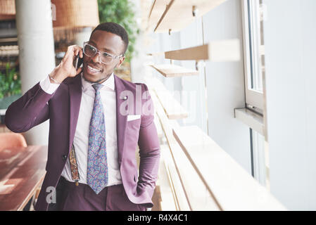 Portrait of a young and handsome African American businessman talking in a suit over the phone - Stock Image