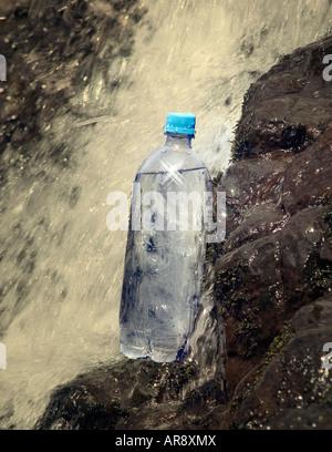 Generic bottle of water near or alongside a waterfall - Stock Image