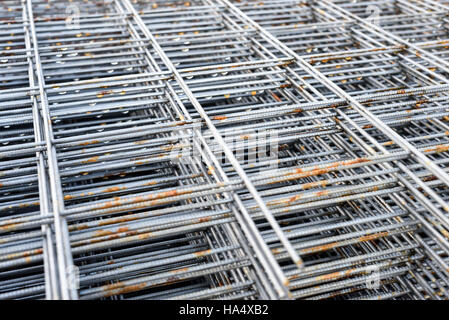 Stacks of square metal reinforcing rods and mesh in natural sunlight. - Stock Image