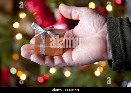 Man holding christmas gift - Stock Image