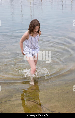 Young girl paddling in the sea in Palamos in Spain - Stock Image