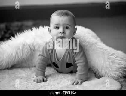 Baby boy in Black and white looking inquisitive in blanket - Stock Image
