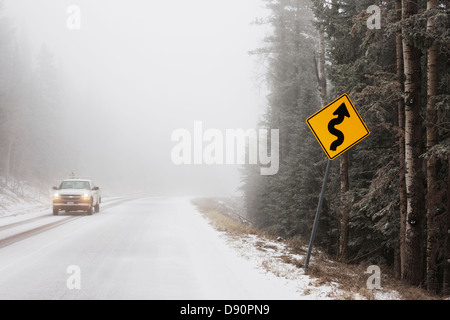 A truck and a curve sign in fog and snow on a mountain road. - Stock Image