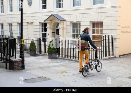 Commuter man with Brompton bicycle walking in Field Court, Grays Inn London England UK  KATHY DEWITT - Stock Image