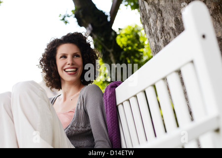 young woman sitting on garden bench - Stock Image