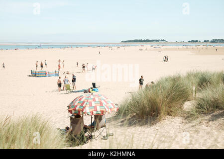 People on a white sand beach at Wells Next The Sea in Norfolk, UK, on a hot Bank Holiday weekend - Stock Image