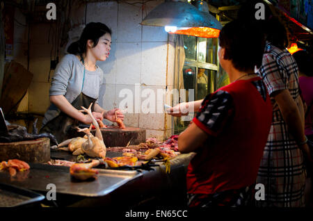 Customer buying fresh poultry from a young female butcher in an Asian market. Indoor market; Guangzhou, China; woman; - Stock Image