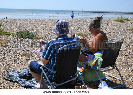 Littlehampton, UK. Saturday 7th July 2018. People relaxing on the beach reading The Sun newspaper on a very warm afternoon in Littlehampton, on the South Coast. Credit: Geoff Smith / Alamy Live News. - Stock Image