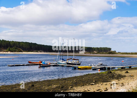 Boats moored by jetty in tidal river estuary in Findhorn Bay harbour. Findhorn, Moray, Scotland, UK, Britain - Stock Image