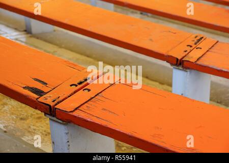 Rows of empty wooden stadium seats . - Stock Image