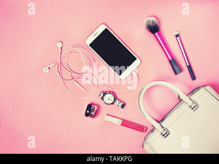 women bag, smartphone, cosmetics, watches on a pink background. view from above. toning - Stock Image