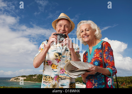 Senior tourist couple with camera and map - Stock Image