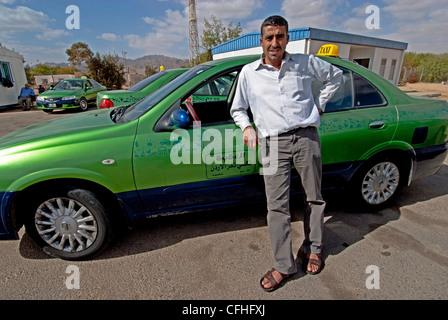 A Jordanian taxi driver  and his cab at the Israel-Jordan Wadi Araba Crossing/South Border connecting Eilat and - Stock Image