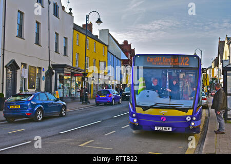 Passengers board a local bus in Cowbridge town centre, en route to Cardiff. Driver collecting fares.Well-to-do rural market town in Vale of Glamorgan. - Stock Image
