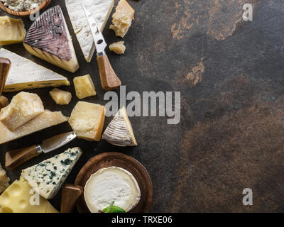 Assortment of organic cheeses on stone background. Top view. Tasty cheese starter. - Stock Image