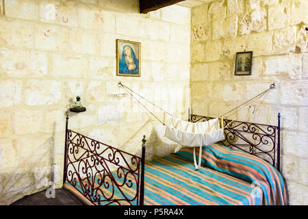 Traditional bedroom with Roman Catholic pictures and a hammock for a baby in a Maltese house. - Stock Image